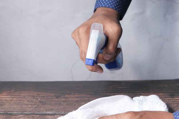 Main tenant un vaporisateur et une table de nettoyage