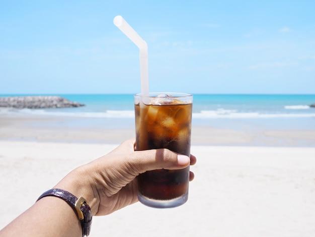Main tenant un verre de boisson gazeuse sur la plage.