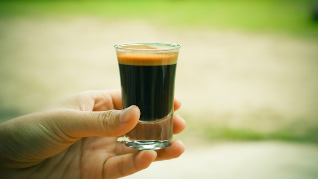 Main tenant un verre de café expresso