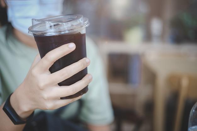 Main tenant un verre de café noir glacé avec le port d'un masque facial le matin