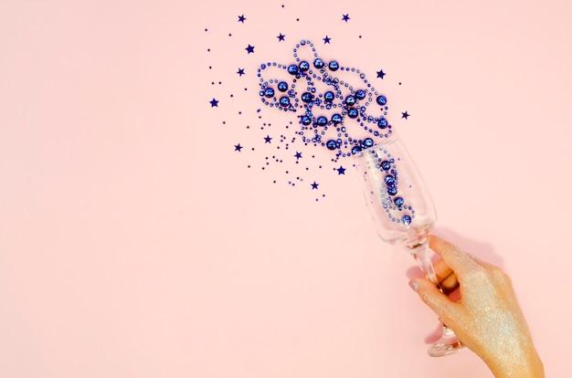 Main tenant un verre avec des confettis
