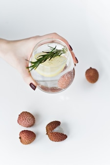 Main tenant un verre d'eau claire avec citron, romarin, litchi.
