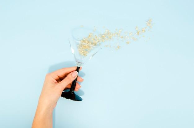 Main tenant un verre avec des paillettes