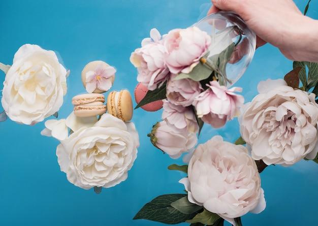 Main tenant le verre avec des peons et des fleurs et des macarons sur fond bleu
