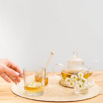Main tenant le verre avec théière et pot de miel
