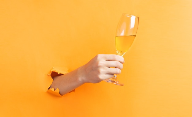 Main tenant des verres à vin dépassant du mur