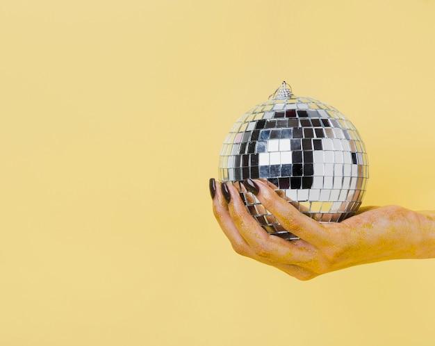 Main tenant une vue de face de boule de noël