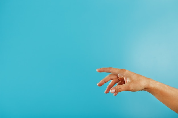 Une main tend la main sur un fond bleu.