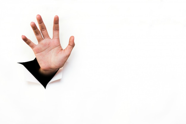 Main tendre la main d'une feuille de papier blanc déchirée