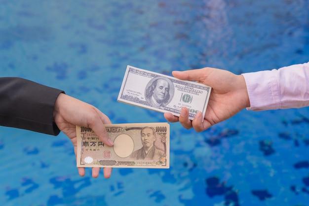 Main tenir des billets de banque en yen japonais et en dollars américains. concept d'échange de devises.
