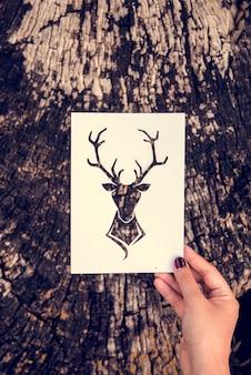 Main tenir le cerf avec des bois sculpture en papier avec le fond de la nature