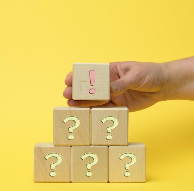 Main tenir le cube en bois avec des points d'exclamation et un point d'interrogation sur une surface jaune