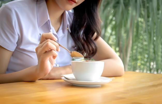Main tenir une cuillère pour mélanger la mousse de café chaud sur une tasse en céramique