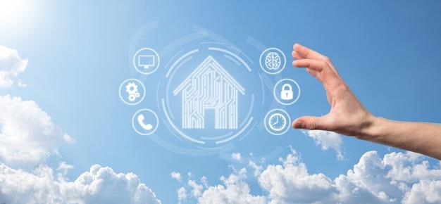 Main tenir l'icône de la maison. concept d'application de maison intelligente contrôlée, maison intelligente et domotique. conception de circuits imprimés et personne avec un téléphone intelligent. concept de réseau internet de technologie d'innovation.