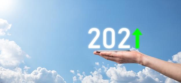 Main tenir l'icône positive 2021 sur fond de ciel.plan d'affaires croissance positive dans le concept de l'année 2021. plan d'homme d'affaires et augmentation des indicateurs positifs dans son entreprise, grandir des concepts d'entreprise.