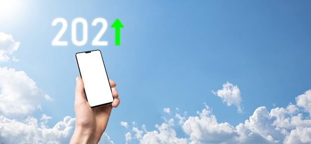 Main tenir l'icône positive 2021 sur fond de ciel. planifier une croissance positive des affaires dans le concept de l'année 2021. plan d'affaires et augmentation des indicateurs positifs dans son entreprise, grandir des concepts d'entreprise.