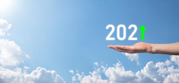 Main tenir l'icône positive 2021 sur fond de ciel. planifier une croissance positive de l'entreprise dans le concept de l'année 2021. plan d'affaires et augmentation des indicateurs positifs dans son entreprise, grandir des concepts d'entreprise.