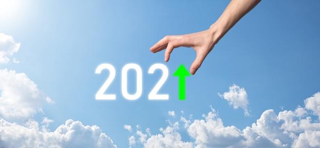 Main tenir l'icône positive 2021 sur la surface du ciel