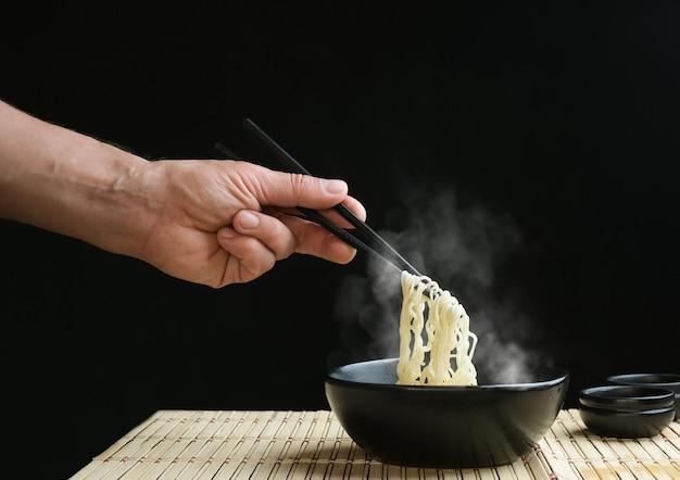 Main tenir des nouilles de baguettes avec de la vapeur sur fond noir concept de malbouffe de nouilles asiatiques