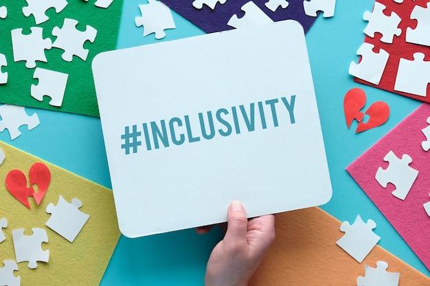 Main tenir la page papier avec texte hashtag inclusivité.