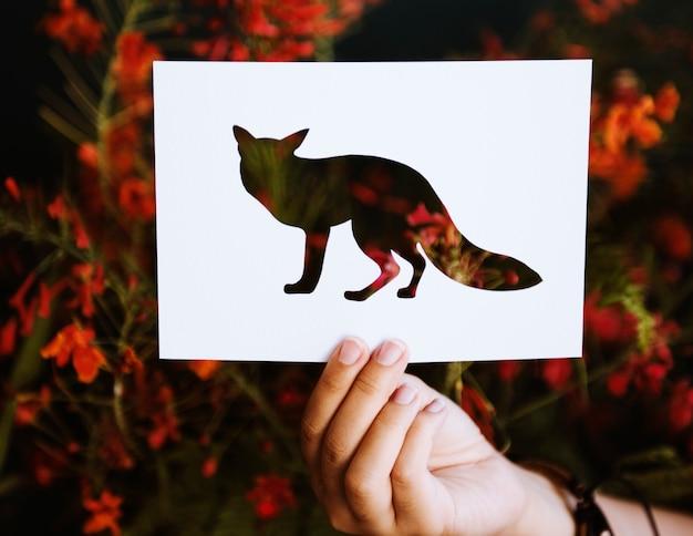 Main tenir le papier de fox sculpture avec le fond de la nature