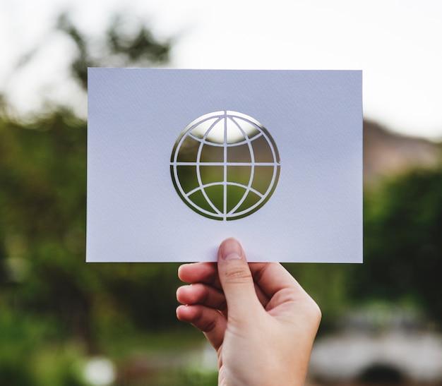 Main tenir le papier globe sculpture sur fond de nature