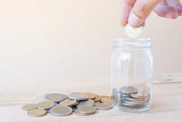 La main tenir la pièce et mettre des pièces de monnaie en verre avec un tas de table en bois coinson - concept d'investissement, d'affaires, de finance et bancaire