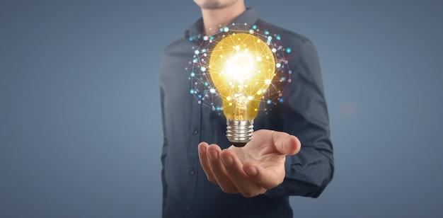 Main de tenue d'ampoule lumineuse, idée, concept d'inspiration d'innovation
