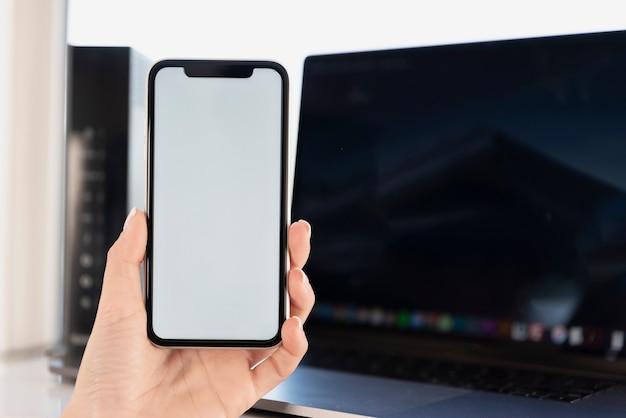 Main, tenue, téléphone, devant, maquette ordinateur portable