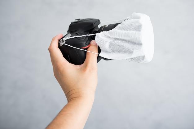 Main tient un appareil photo protégé par un masque. protection covid / coronavirus pour les photographes