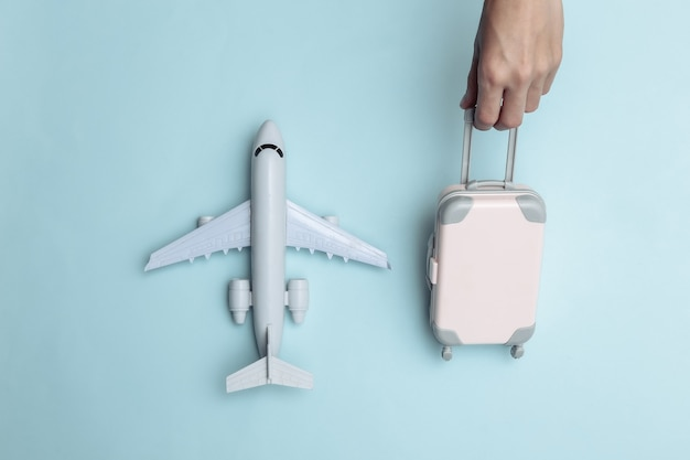 La main tient des bagages de voyage de mini marionnettes et un avion sur fond bleu. temps de voyage. vue de dessus