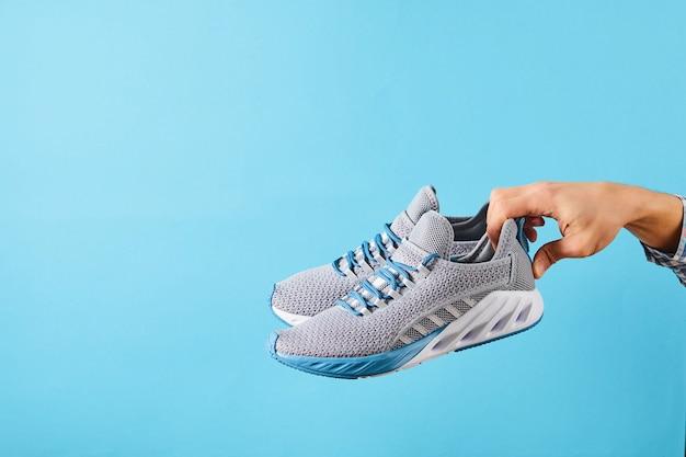 Main tient des baskets de course grises suspendues sur fond bleu pastel. main avec une nouvelle chaussure de sport. chaussures de course stables et amortissantes. fermer.