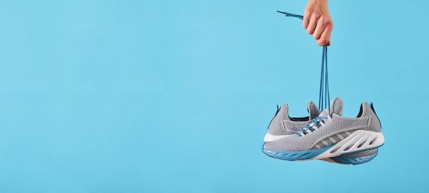 Main tient des baskets de course grises suspendues par les lacets sur fond bleu pastel. main avec une nouvelle chaussure de sport. chaussures de course stables et amortissantes. fermer.