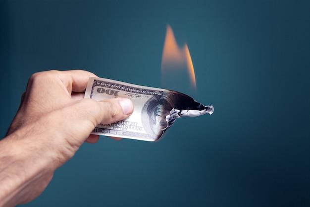 La main tient un billet d'un dollar qui brûle