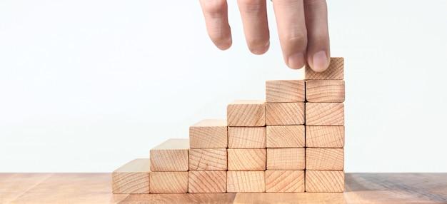 Main tient des blocs de bois sur fond blanc