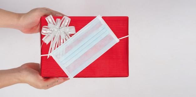 La main tient un cadeau ou un emballage cadeau avec masque facial et papier de couleur rouge sur fond blanc.
