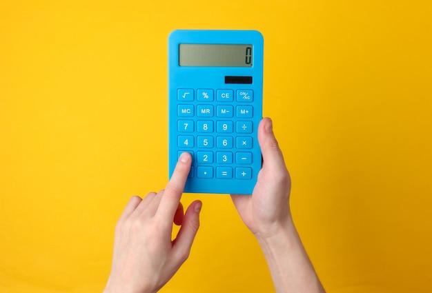 Main tient la calculatrice bleue sur jaune.
