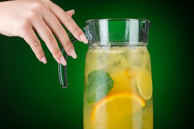 La main tient une carafe avec une boisson froide aux agrumes. jus tropical d'été