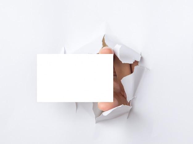 Main tient une carte blanche à travers fond de papier déchiré blanc