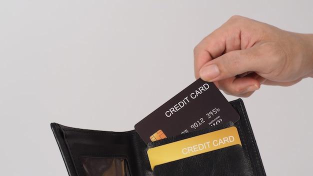 La main tient une carte de crédit noire. couleur de carte de crédit or dans un portefeuille noir isolé sur fond blanc.
