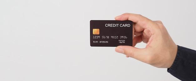 La main tient une carte de crédit noire isolée sur fond blanc. main d'homme asiatique.