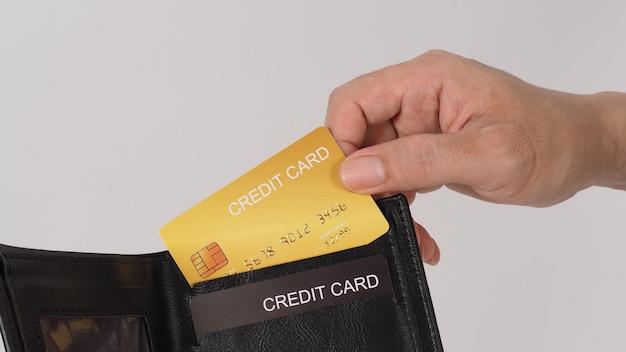 La main tient une carte de crédit en or. couleur noire en portefeuille isolé sur fond blanc.