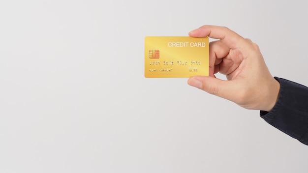 La main tient une carte de crédit en or isolée sur fond blanc. main d'homme asiatique.