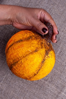 Une main tient une citrouille en papier mâché orange maison pour halloween sur une surface de jute