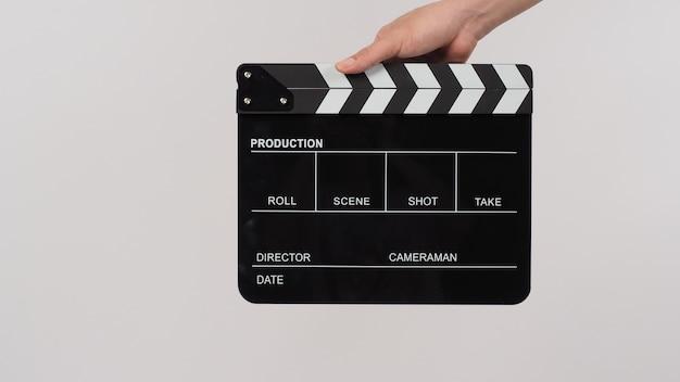 La main tient un clap noir ou une ardoise de film sur fond blanc.