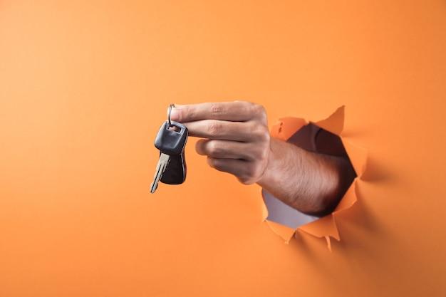 Main tient les clés de voiture sur fond orange