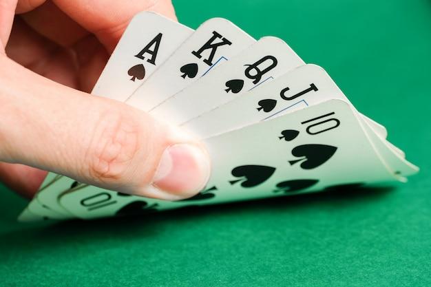Main tient une combinaison au poker - quinte flush royale sur le vert.