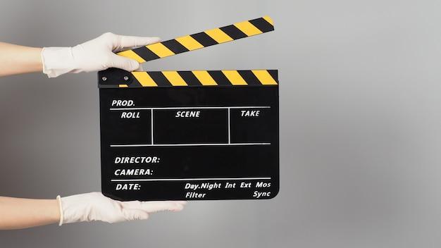 La main tient la couleur du clap jaune et noir ou le clap du film et porte un gant médical blanc sur fond gris.
