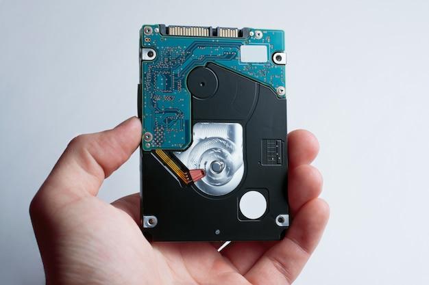 Une main tient le disque dur sur le fond blanc