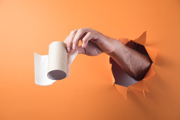 Main tient du papier toilette sur fond orange